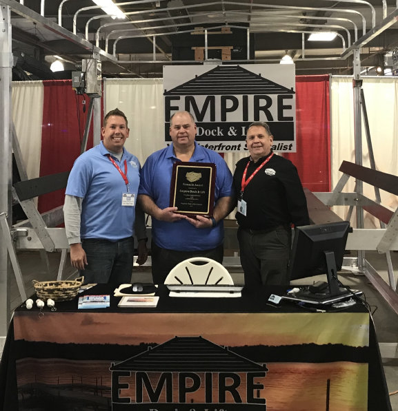 Picture of founder Joe MacVittie at center with son Joey and Scott Feighner of Feighner docks.  Joe is being presented with a Top 